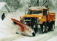 Snow plow pushing snow down street
