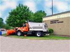 Dump truck with plow next to building with lettering - Shrewsbury Municipal Garage